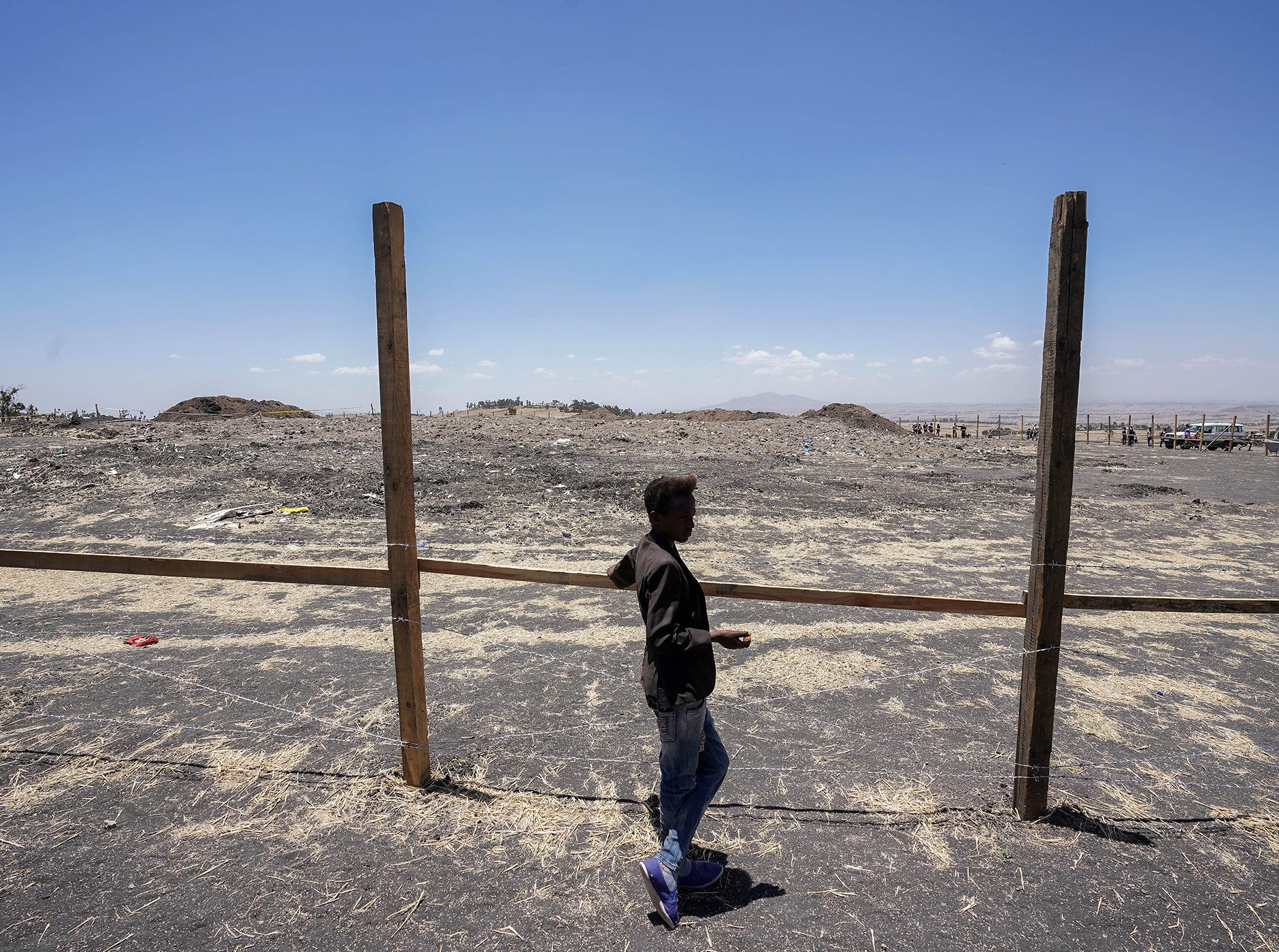 A young boy stands at the fence around the crash site of Ethiopian Airlines Flight 302 during the Asrahhullet or Tulluferra ceremony on March 21, 2019 in Ejere, Ethiopia.