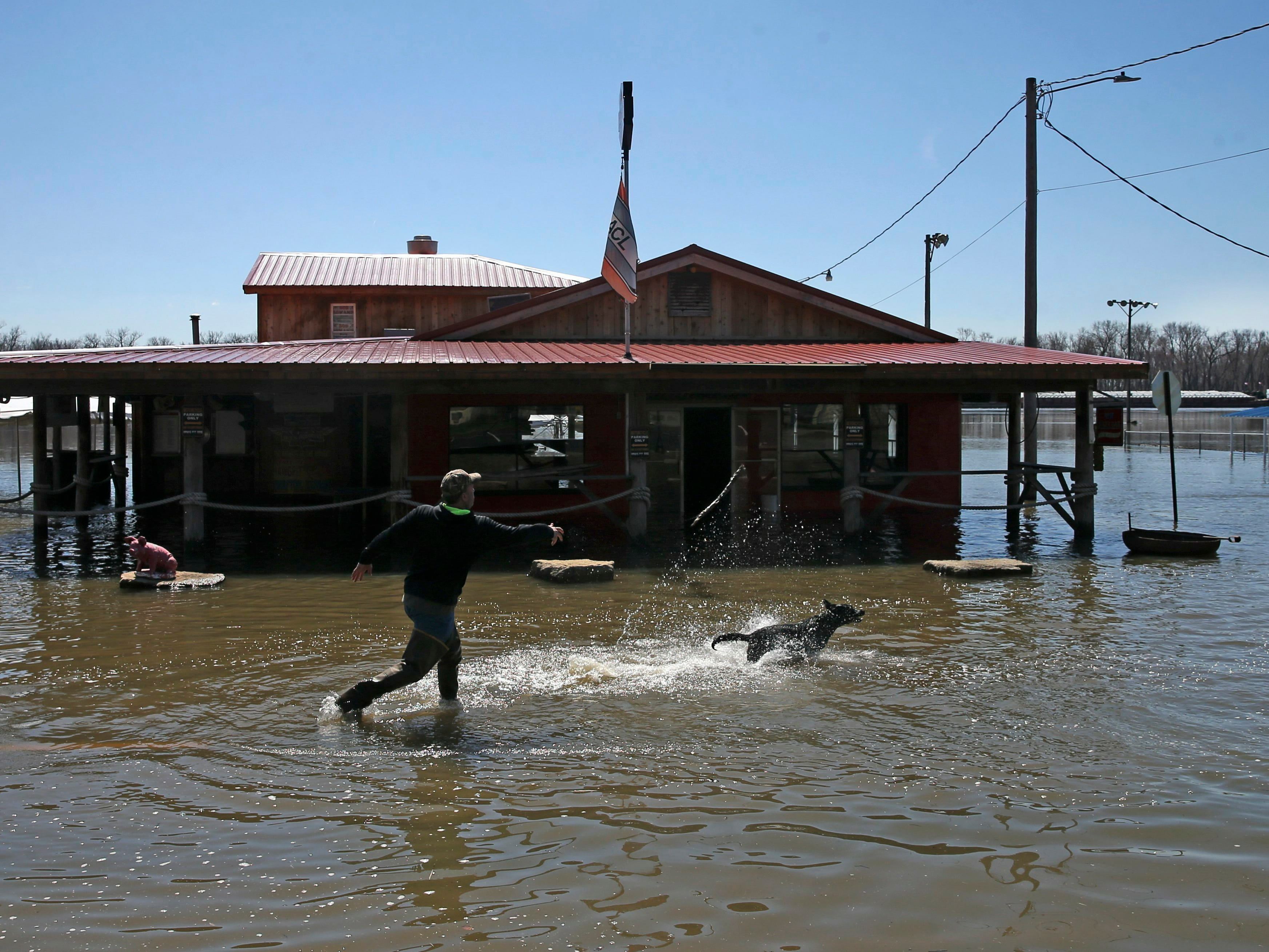 """Cory Wiemelt of Quincy, Ill., the new owner of the Hawg Pit BBQ, passes the day playing fetch with his dog Abbie, while keeping an eye on his bar located along a flooded part of W. Main Street, Tuesday, March, 26, 2019,  in Grafton, Ill. """"We are located at the lowest spot in town. I knew that when I bought the place,"""" said Wiemelt. """"I just have to wait for the water to go down before I can start cleaning up,"""" he said."""