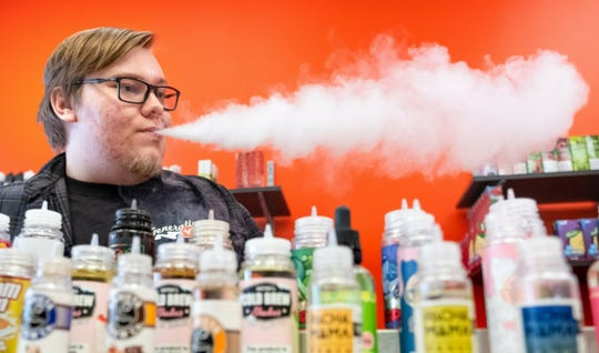 In this Nov., 2018 file photo, shift manager Shaun Miller exhales vapor while working behind the vape bar at Generation V in Omaha, Neb. An apparent surge in vaping among Nebraska teenagers is prompting a new push from lawmakers to raise the age limit on e-cigarettes from 18 to 21 and ban their use in bars, restaurants and workplaces. School officials say the crackdown would help them fight the growing use of e-cigarettes among young people.