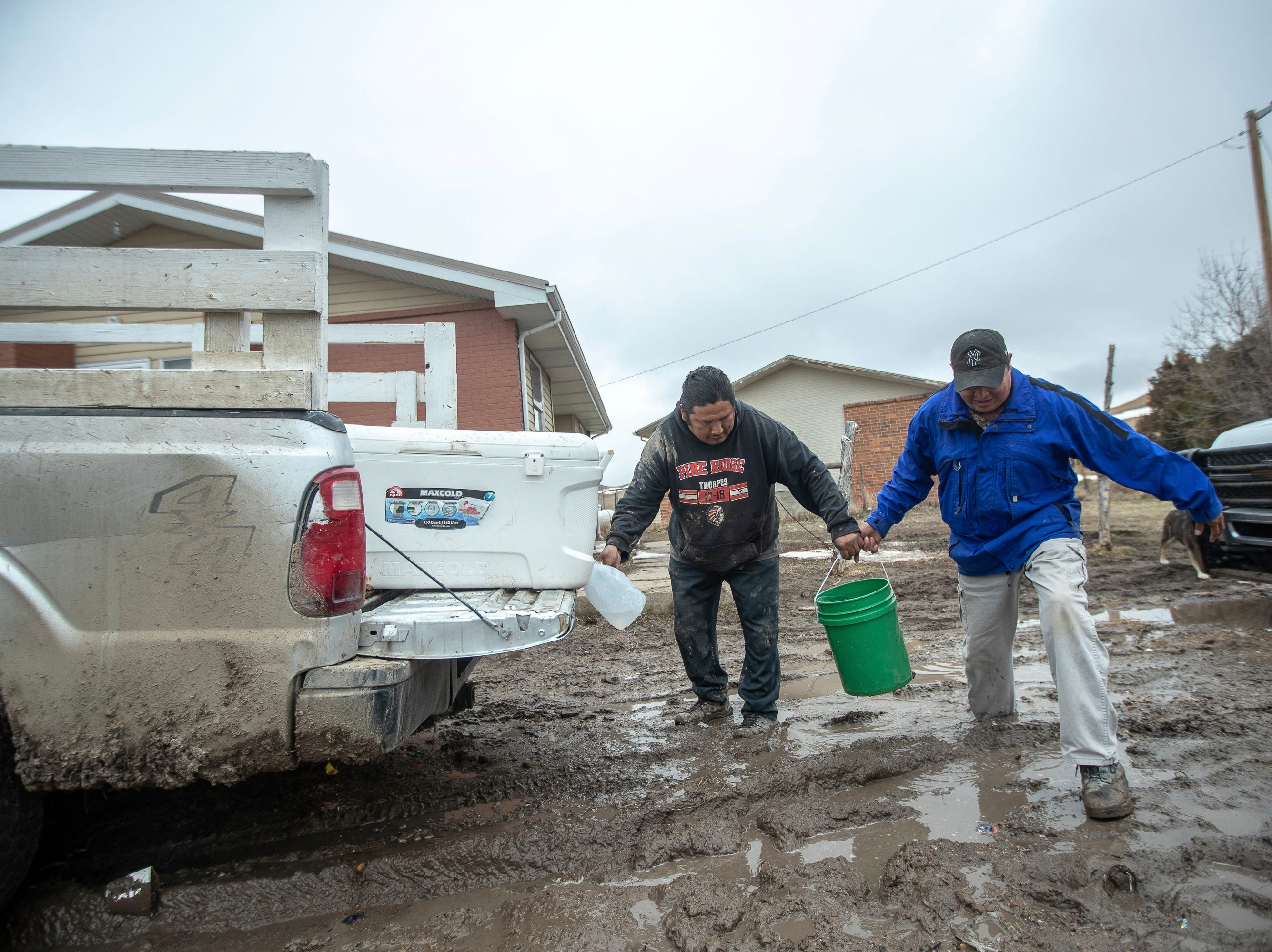 In this Monday, March 25, 2019 photo, tribal employees bring water, to elders and others who were stranded in their homes on the Pine Ridge Indian Reservation  near Porcupine, S.D., following spring flooding.
