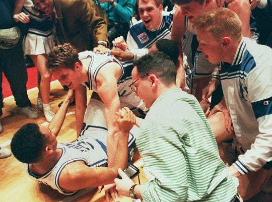 Duke's Christian Laettner, top, who scored the game-winning basket in overtime, celebrates with teammate Grant Hill on the floor of the Philadelphia Spectrum as teammates and fans crowd around in this March 28, 1992 photo.  Duke, the defending national champions, defeated the University of Kentucky 104-103 to advance to the Final Four.  Six years after Laettner's shot gave Duke a breathtaking victory, the two superpowers will meet again in the NCAA South Regional final Sunday, March 22,1998.