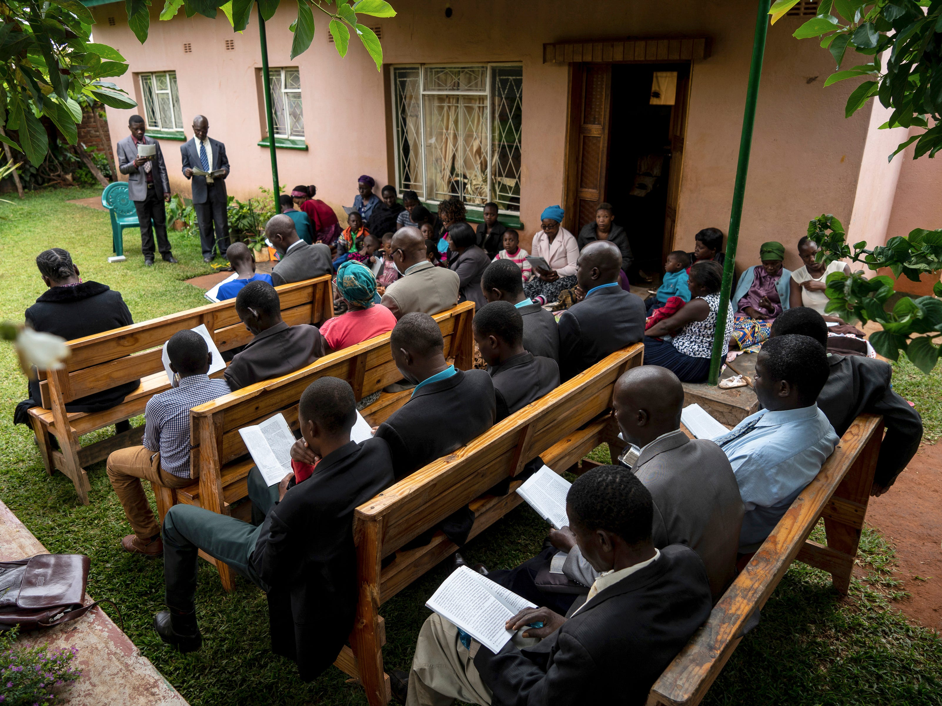Members of the Jehovah's Witnesses church hold a service at a private home in Chipinge, Zimbabwe Sunday March 24, 2019 after their church building was destroyed by Cyclone Idai. The death toll has risen above 750 in the three southern African countries hit 10 days ago by the storm, as workers restore electricity, water and try to prevent outbreak of cholera, authorities said Sunday.