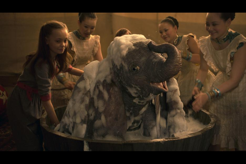 "Milly Farrier (Nico Parker) gives a baby elephant a bath in ""Dumbo."""