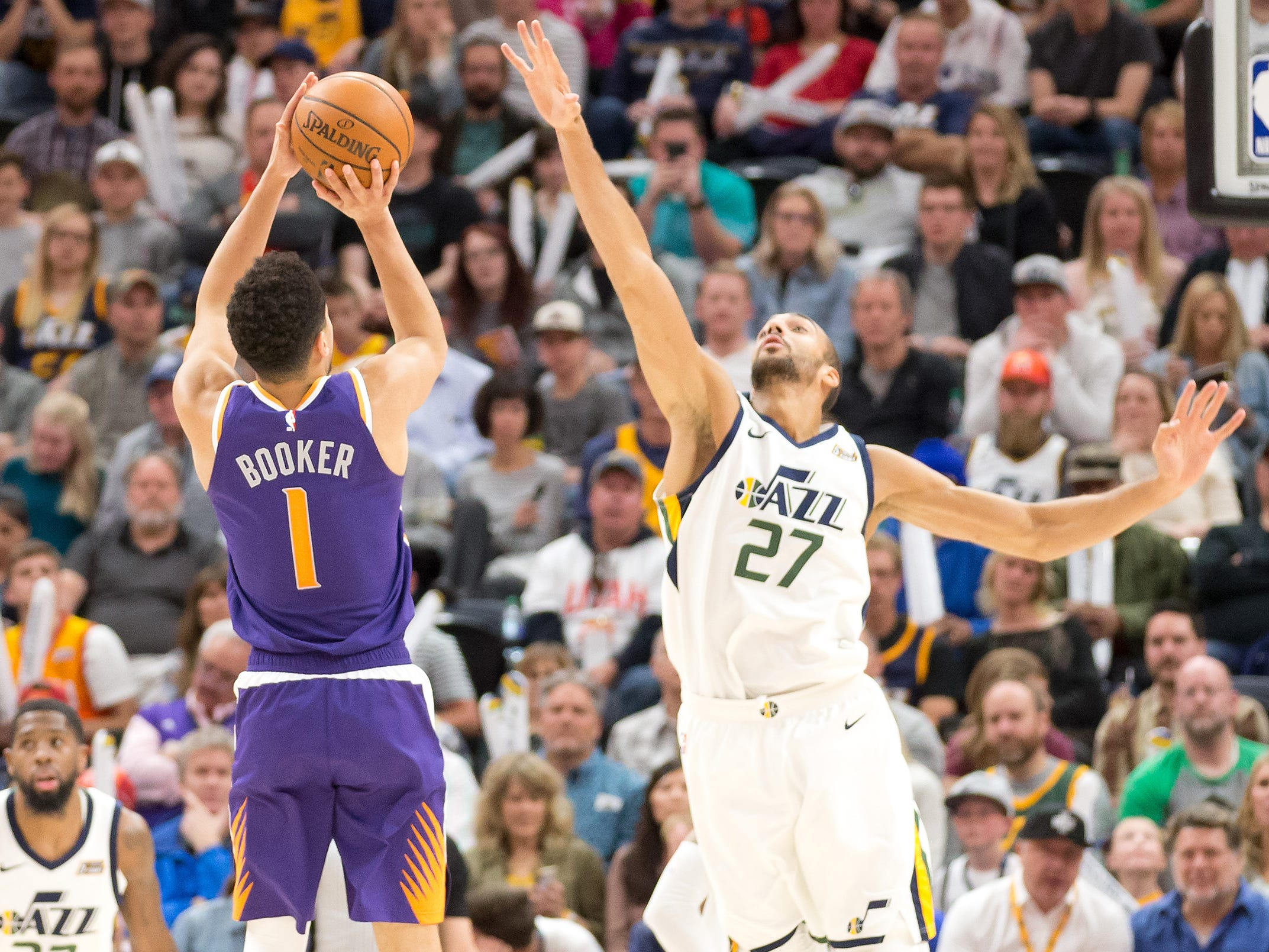 March 25: Suns guard Devin Booker (1) shoots over the out-stretched arm of Jazz defender Rudy Gobert (27) on his way to 59 points in Salt Lake City.