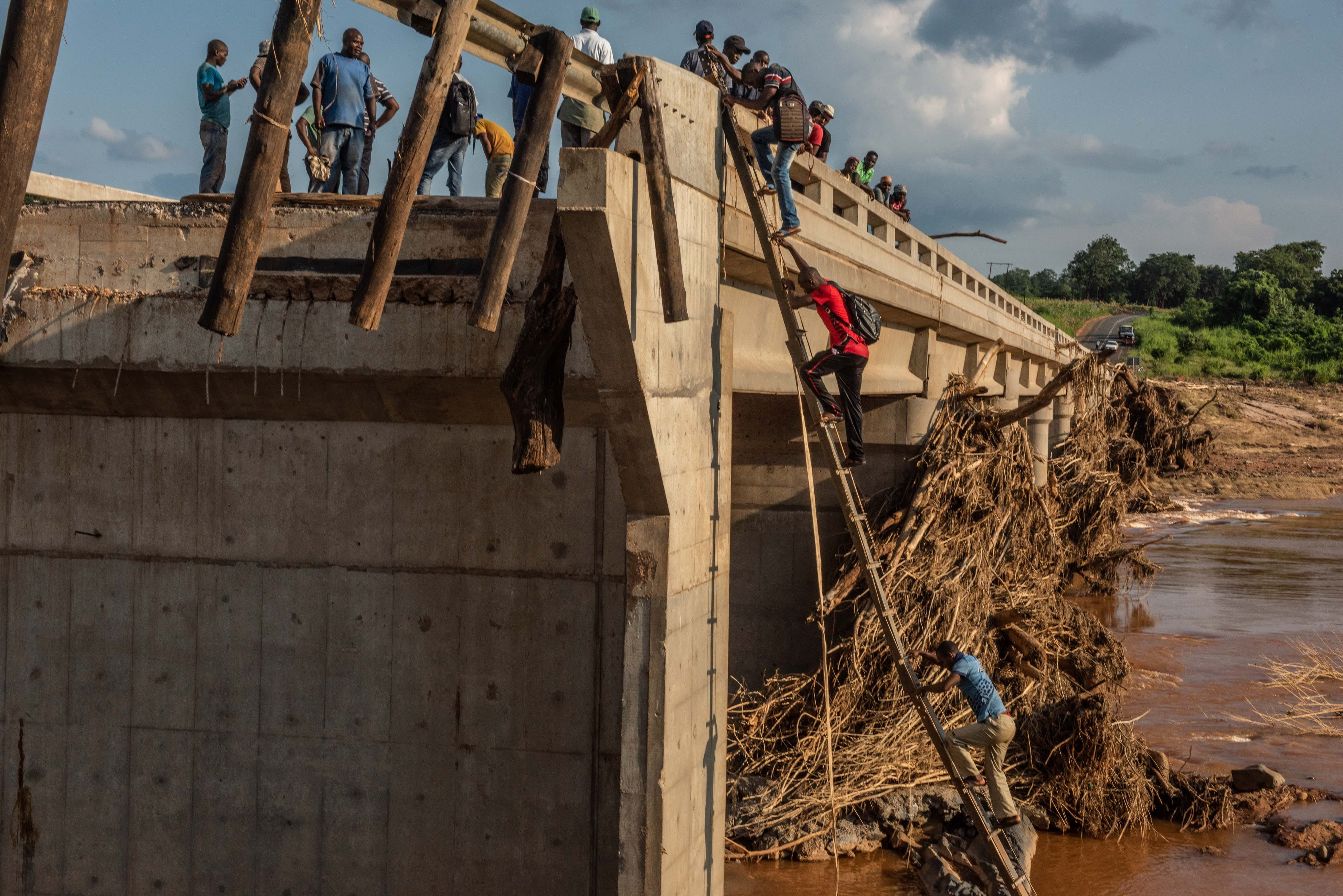 People climb to the top of a broken bridge, damaged during Cyclone Idai, across the Lucite River on March 26, 2019, outside of Magaro, Mozambique. The storm caused the river to overflow flooding nearby villages. At least 156 bodies have been found in the surrounding area, with witnesses recounting seeing bodies of humans and animals flowing down the river.