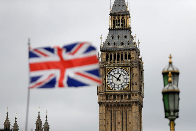 "A British flag flies near the ""Big Ben"" clock tower of Parliament in London."