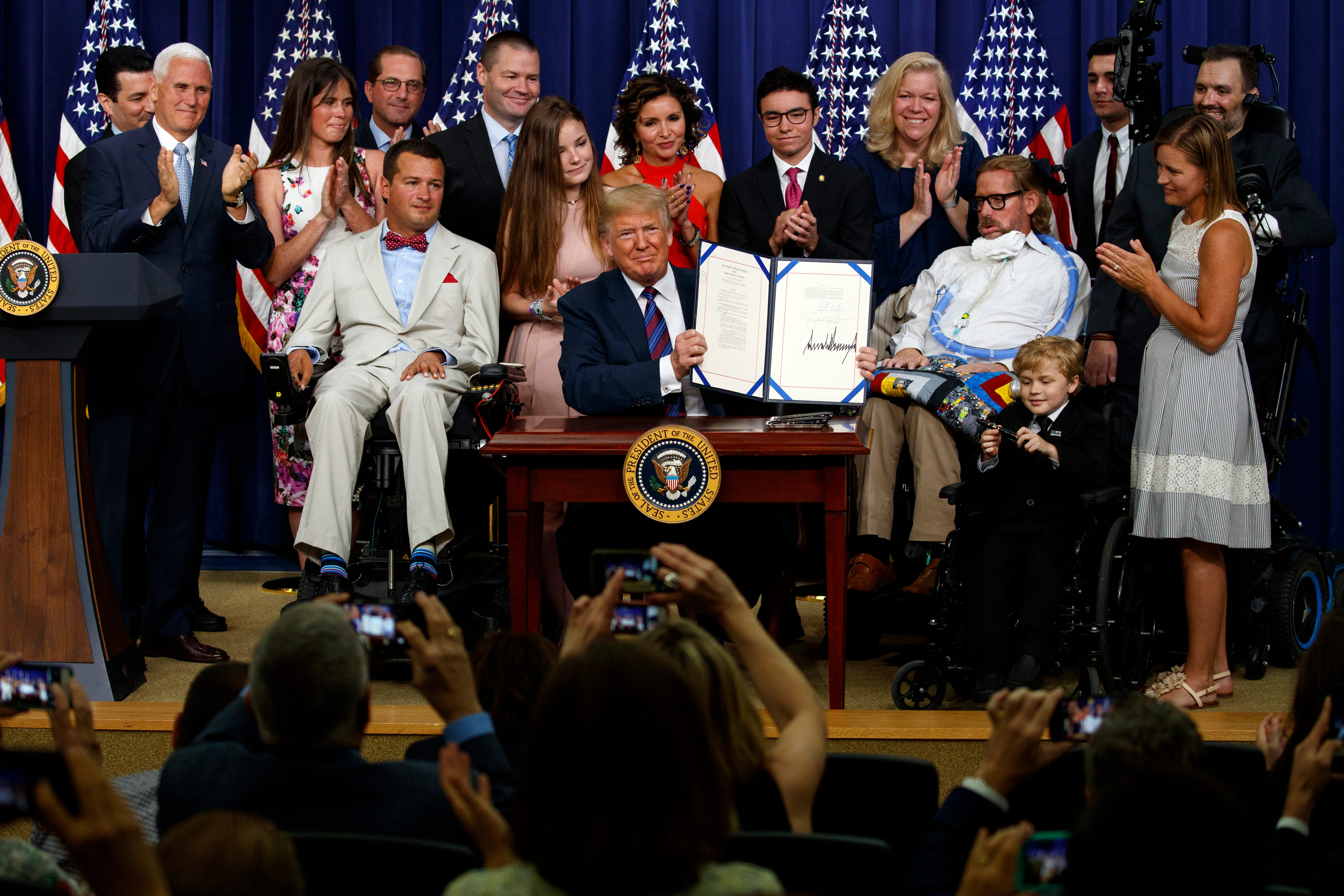 """President Donald Trump holds up the """"Right to Try"""" act after signing it in the South Court Auditorium on the White House campus, on May 30, 2018 in Washington."""