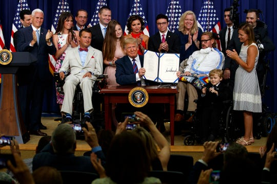 "President Donald Trump holds up the ""Right to Try"" act after signing it in the South Court Auditorium on the White House campus, on May 30, 2018 in Washington."