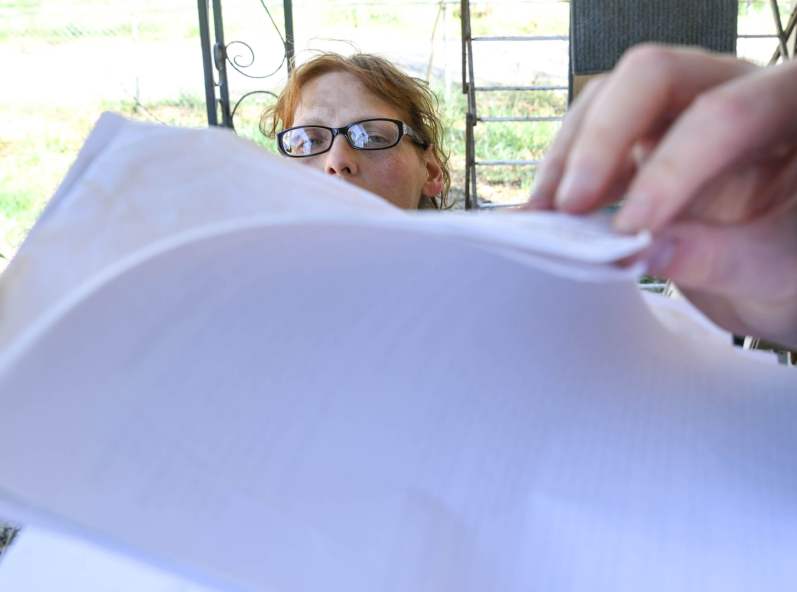 Kristy Drees of Anderson sits near her son Donald flipping through documents of recent water bills from Homeland Park Water Company in Anderson in March. She didn't expect her water bill in Homeland Park to exceed the typical monthly bill around $40 to $50. The problems with the water company and courtroom battles with her landlord while being unemployed she says is stressful.