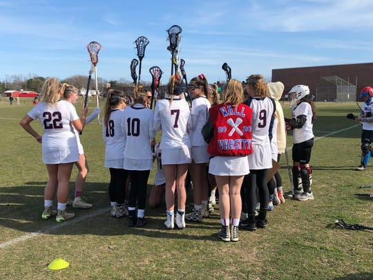 The Wall girls lacrosse team chats at halftime during its game with Freehold Township on March 27, 2019 at Wall High School