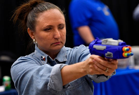 Judith Puryear of Senter Realtor takes aim at a target with a toy gun in the Hilton Garden Inn booth at Business Expo.