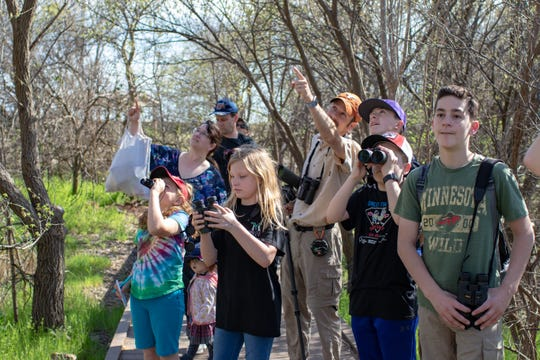 Jay Packer points out where to find a Pine Siskin to a group of young birders on the boardwalk at Kirby Lake.