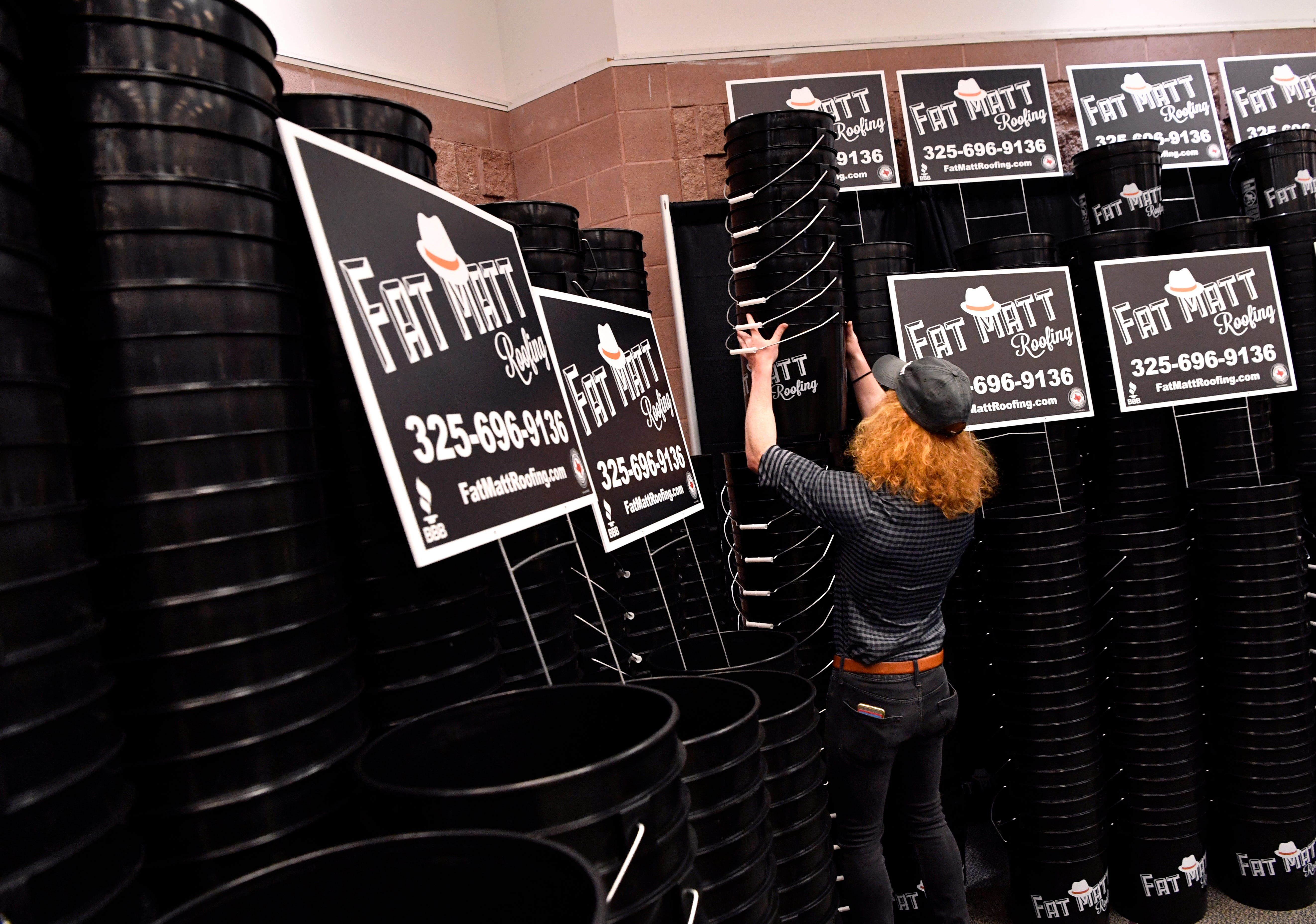 Evan Dickson lifts a stack of buckets branded with the Fat Matt Roofing logo during Wednesday's Business Expo.
