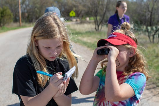 Payton Burch (left) writes down the birds she's seen while Avonlea Condra looks at a relative of the cardinal called the Pyrrhuloxia.