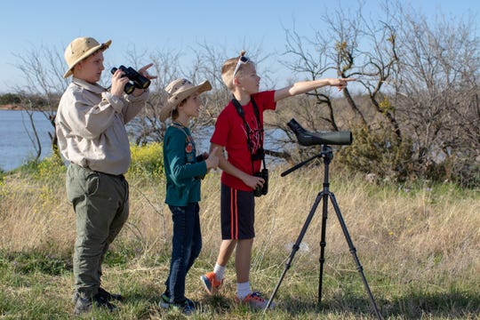 Matthew Gray, Mark Gray, and Owen Crawford react to a Mourning Dove flying away at Kirby Lake.