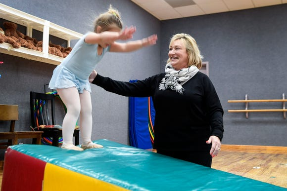 Angie Henley, owner of Angie's Dance Academy, helps Parker Messer, 3, do a somersault March 26, 2019 in Clyde. Her son, Landon, an athlete at Tuscola High, grew up spending time at the dance studio and dancing with his mother.