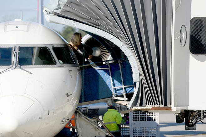 Passengers disembark from a Delta Airlines flight as their luggage is unloaded from under the plane at the Asheville Regional Airport on March 27, 2019.