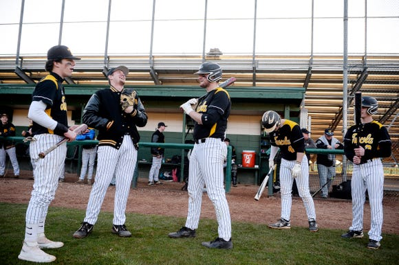 Landon Henley, second from left, laughs with his teammates before the game at Reynolds March 19, 2019.