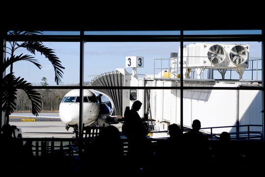 Travelers wait for their flights at the gate as passengers disembark from a plane at the Asheville Regional Airport on March 27, 2019.