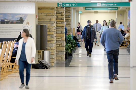 Passengers walk between gates at the Asheville Regional Airport on March 27, 2019.