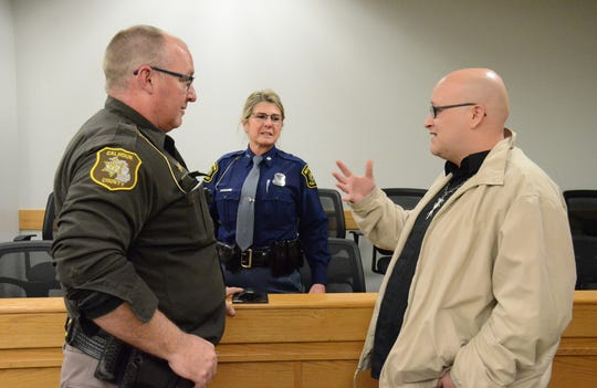 Seigal Washburn, right, talks with Calhoun County Sheriff Department Deputy Kevin Mahan and Michigan State Trooper Kristi Angelo after Mental Health Court graduation.