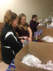 Cortney Briggs, Trista Evans and Andrea Marble volunteer with Windsor Knight Pack at Windsor High School.