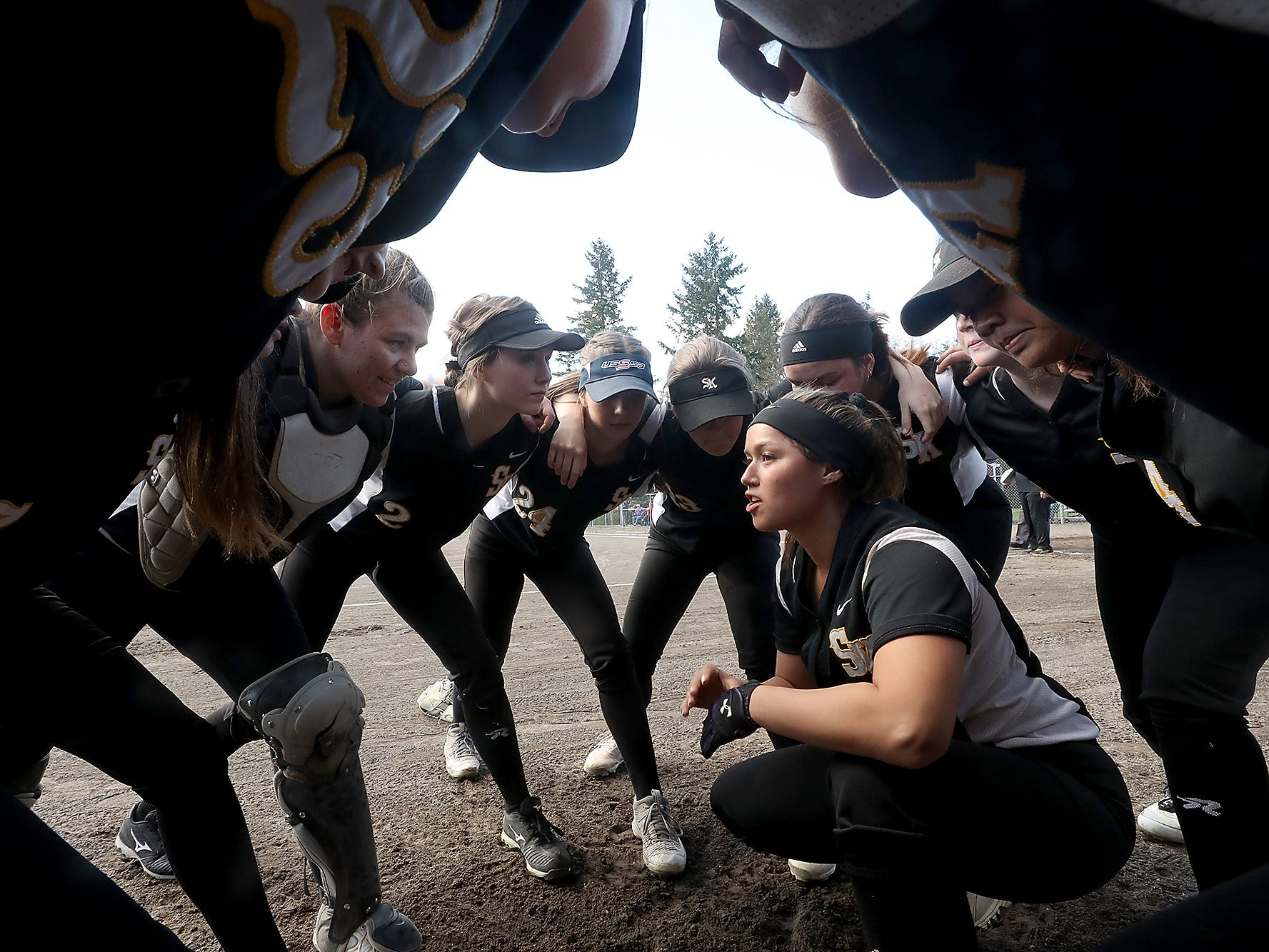 South Kitsap softball Captain Jordynn Lawrence crouches in the middle of the circle as she gives a pep talk to the team before their game against Puyallup on Tuesday, March 26, 2019.