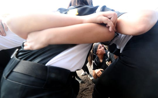 South Kitsap softball captain Jordynn Lawrence crouches in the middle of the circle as she gives a pep talk to the team before their game against Puyallup on March 26. The Wolves entered the week with a 6-1 record.
