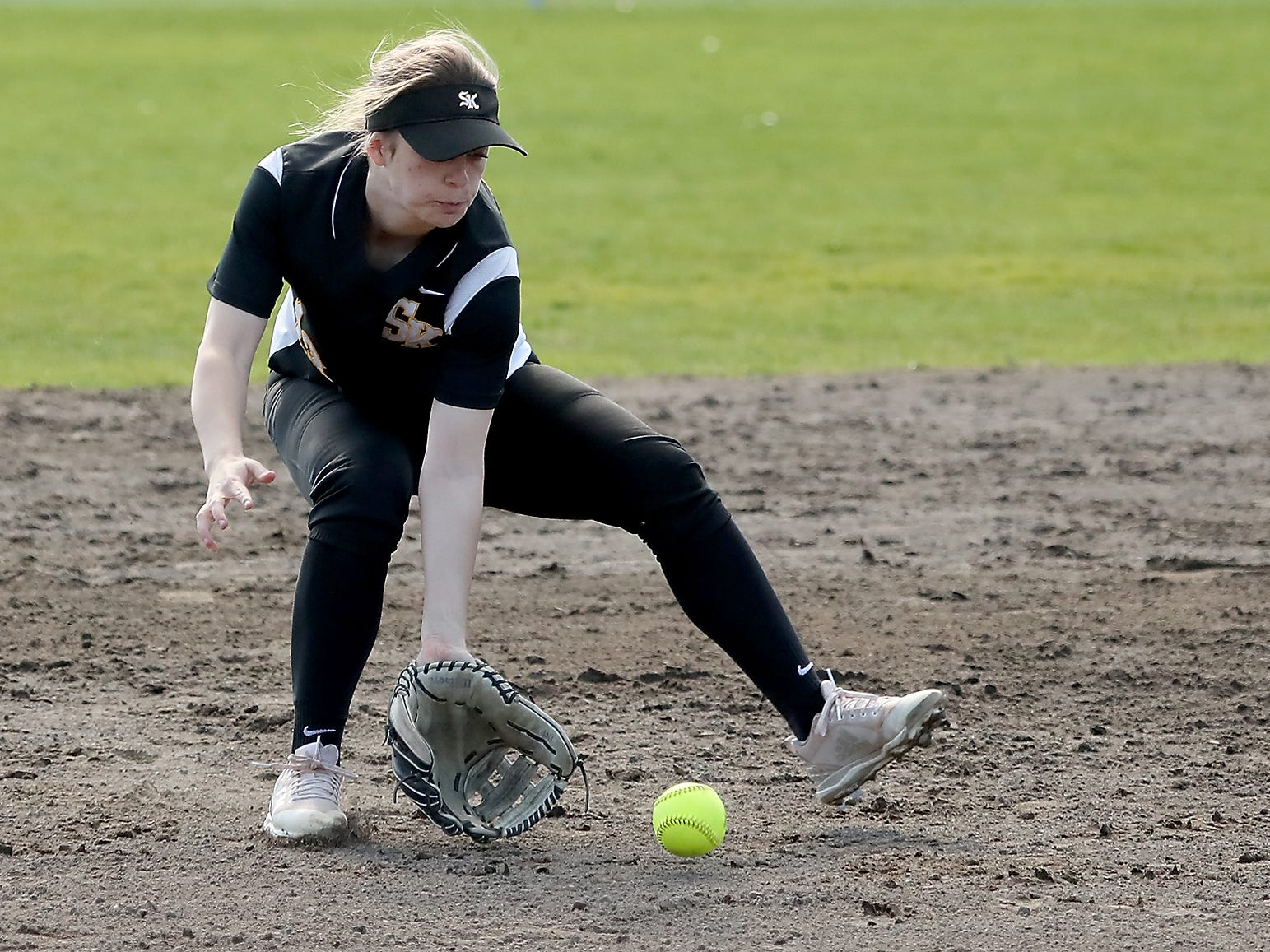 South Kitsap's Kaitlynn Johnston scoops up a ground ball against Puyallup on Tuesday, March 26, 2019.