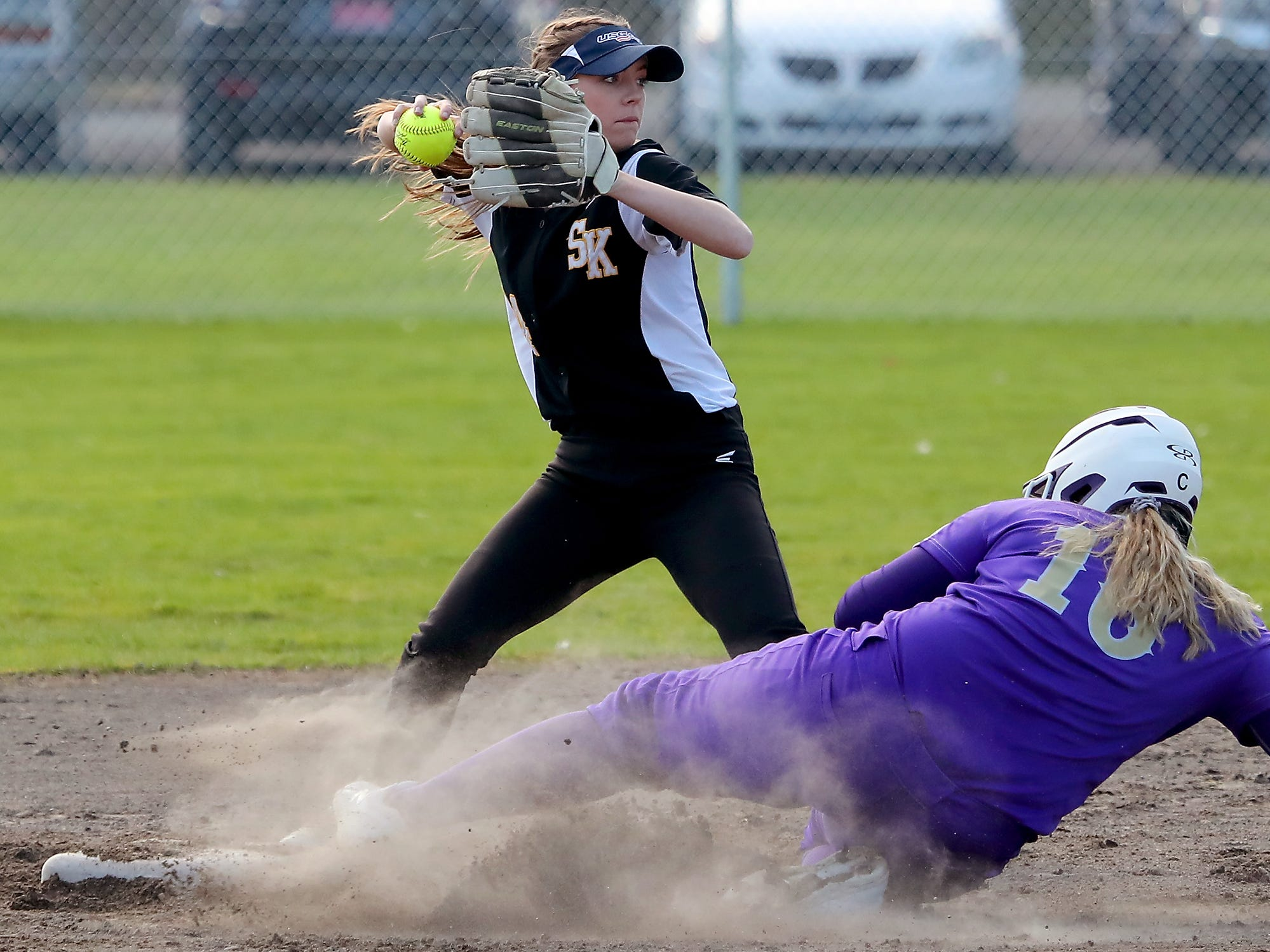 South Kitsap's Teanna Lathum turns to throw the ball to first for a double play as Puyallup's Sidney Booth is out wiht a slide into second during their game on Tuesday, March 26, 2019.