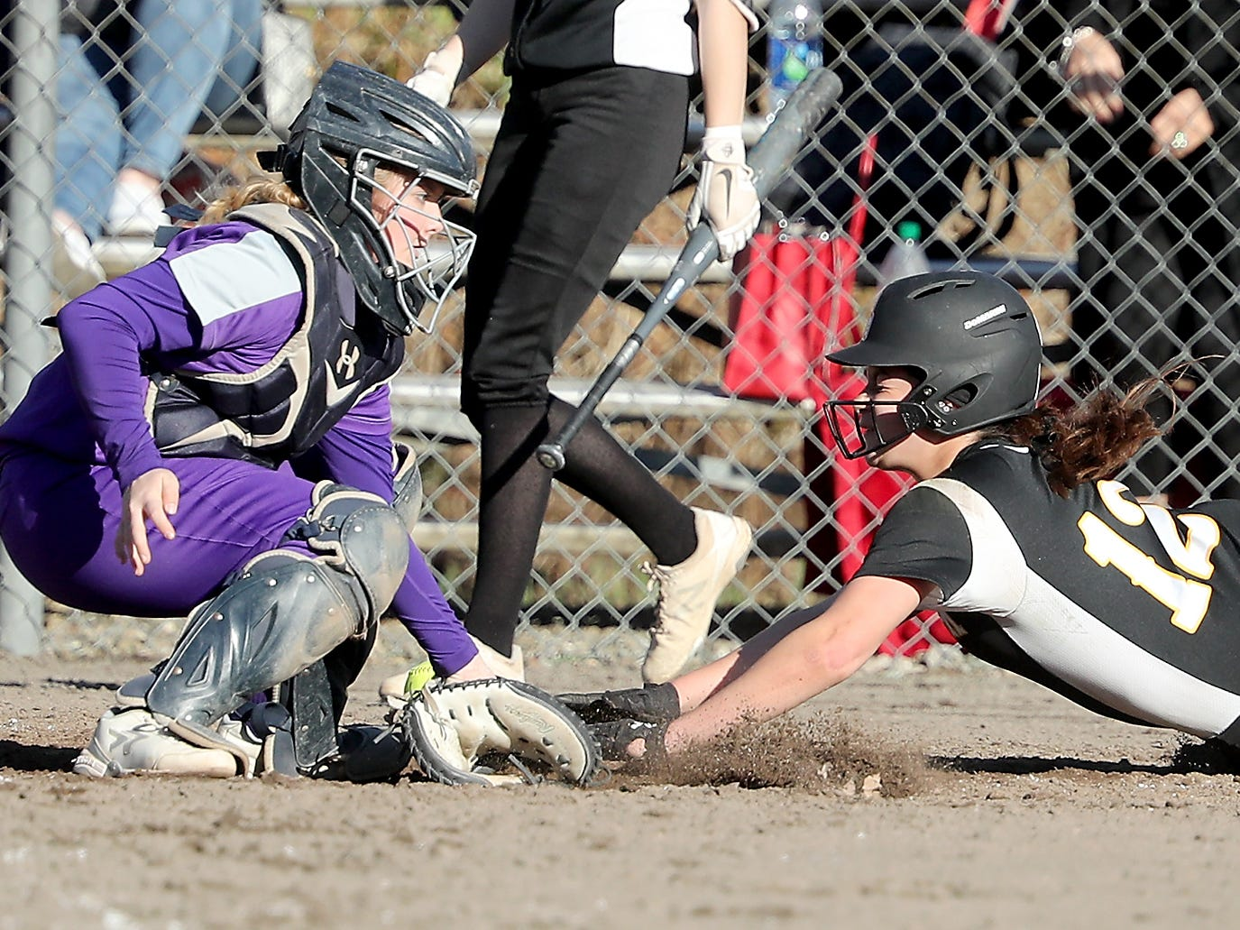 South Kitsap's Sarah Hoyt (12) dives into home and beats the throw to Puyallup's Sierra Edwards on Tuesday, March 26, 2019.