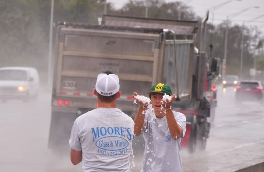 Not sure if Jordan Wallace and Adam Rossbach, who work for Moore's Glass & Mirror have ever seen snow before. They stopped by some piled up hail on US 1 near Horse Creek on US 1 to play in it on their way to a job.