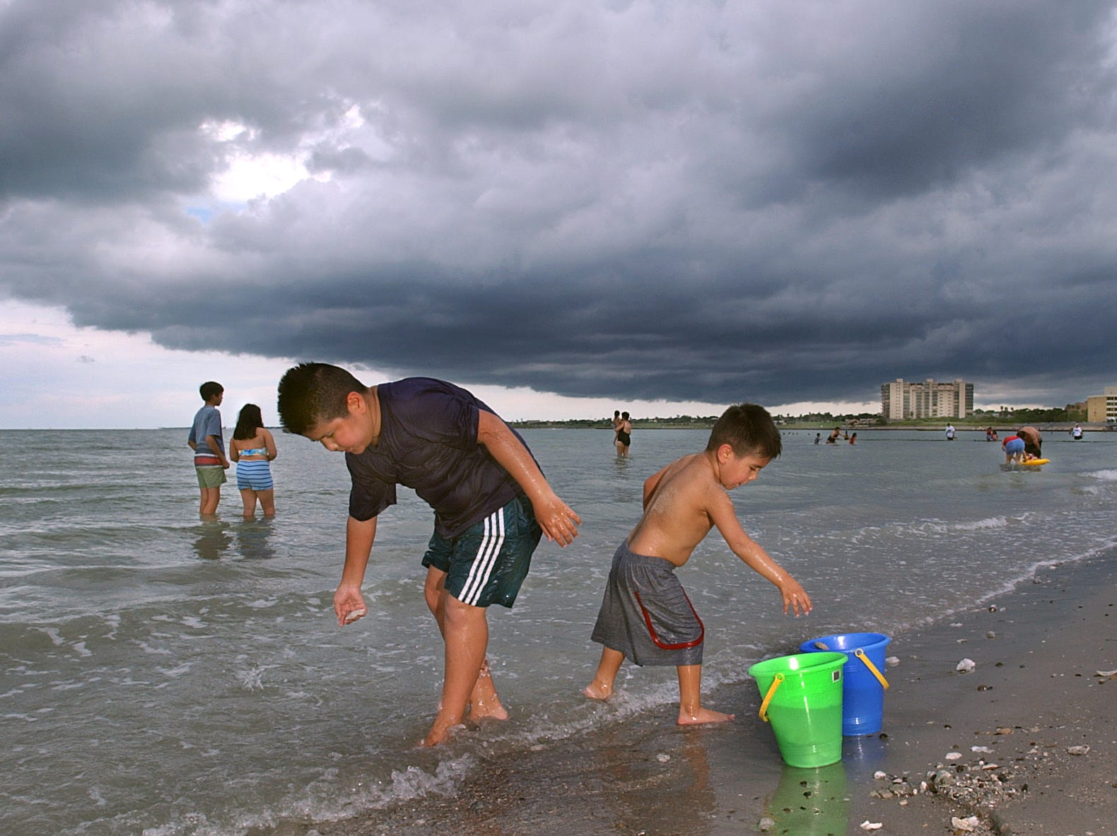 Brothers Horacio Alaniz (left) and Brandon Alaniz (right) collect shells on the new beach at McGee Beach oin downtown Corpus Christi as dark storm clouds move over the bayfront Monday, Sept. 1, 2003.