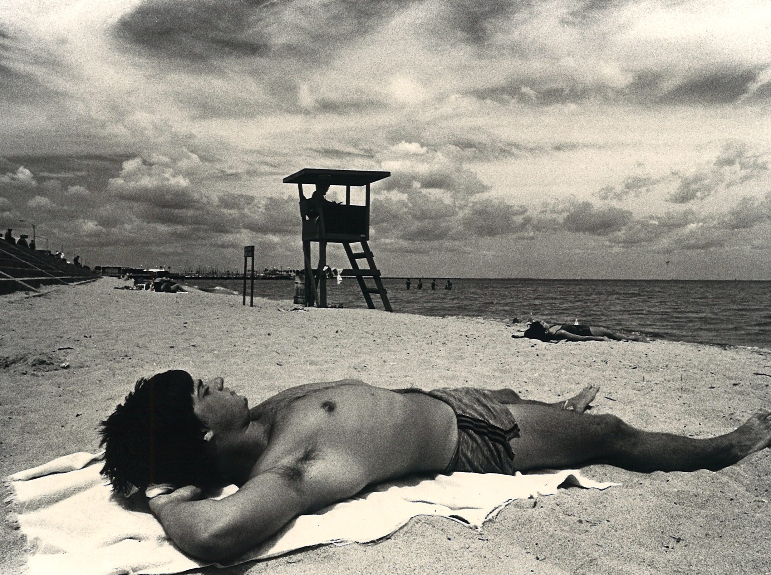 Floyd Goodrich of Austin enjoys the sun on McGee Beach in downtown Corpus Christi on Aug. 17, 1983 despite warnings for Hurricane Alicia churning in the Gulf of Mexico.