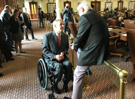 Texas Gov. Greg Abbott, left, talks with state Rep. Dan Huberty on the House floor as the debate on the 2020-2021 budget begins on March 27, 2019.