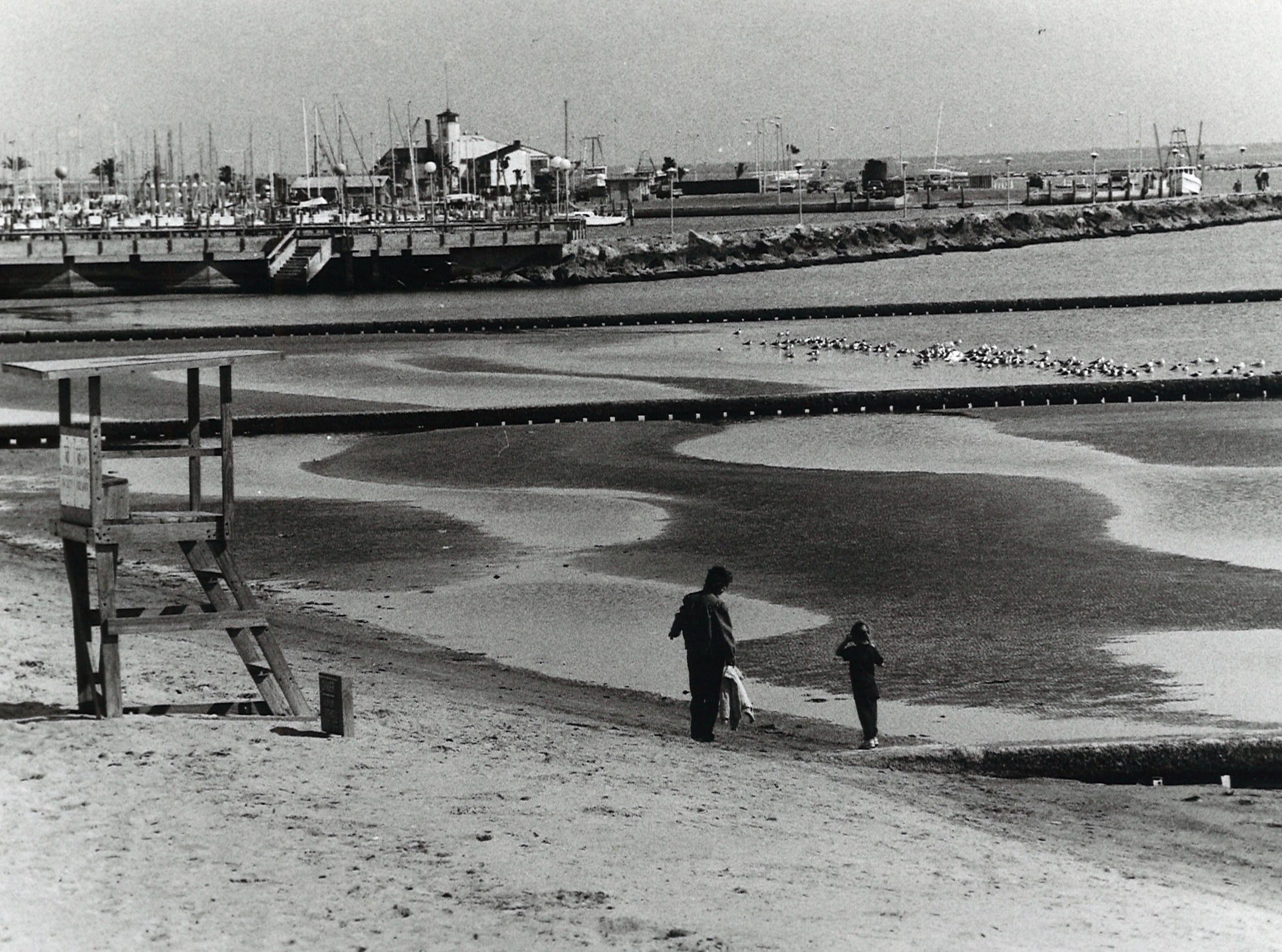 Gwen Smith and daughter, Jesse, both visiting from Hamlin, Texas, walk along the water's edge at McGee Beach in downtown Corpus Christi on Feb. 27, 1992.