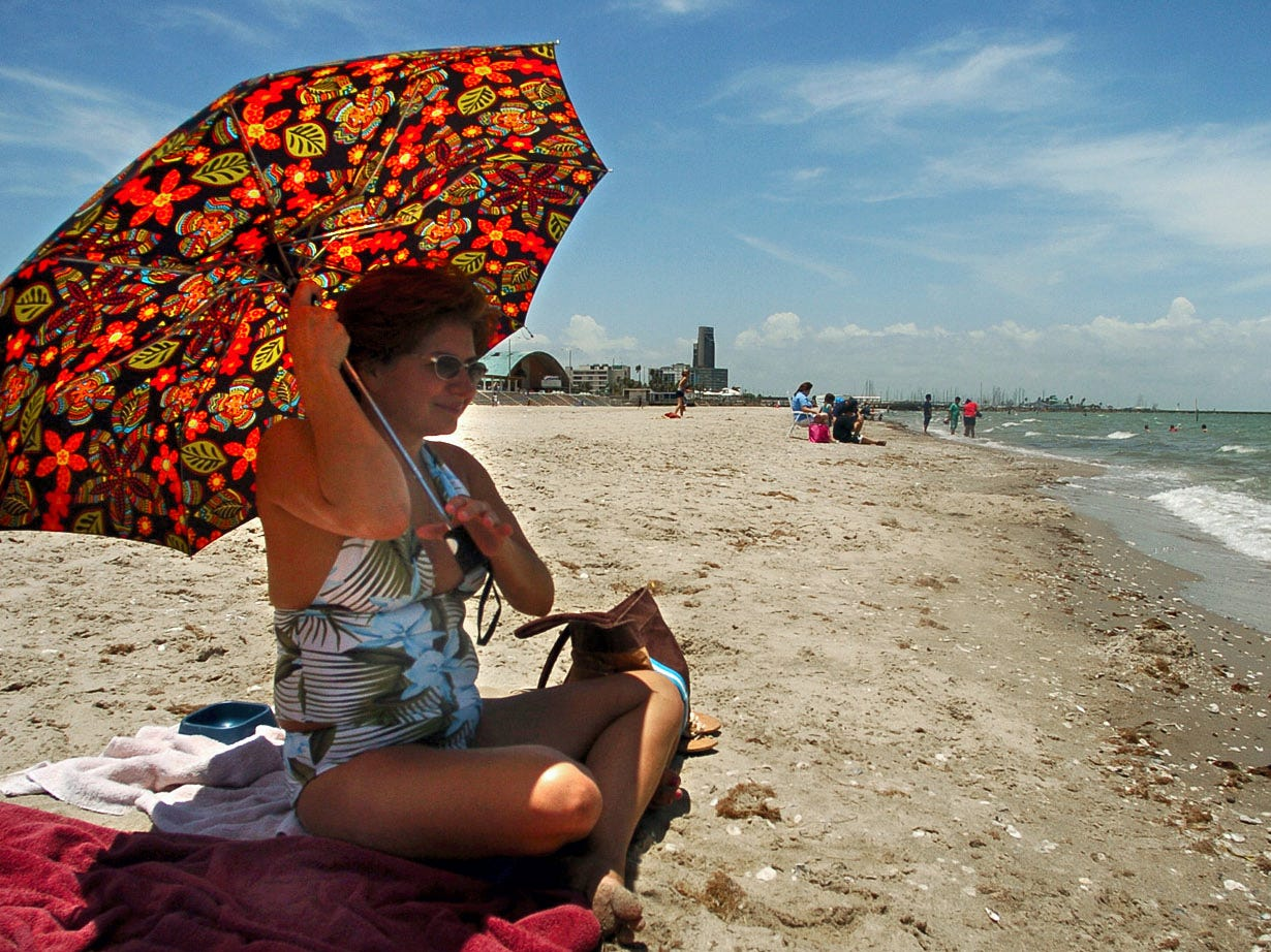 Thelma Talamante of Corpus Christi uses an umbrella to protect herself from the mid-day sun as she enjoys a relaxing day on McGee Beach in downtown Corpus Christi on Tuesday, June 12, 2007.