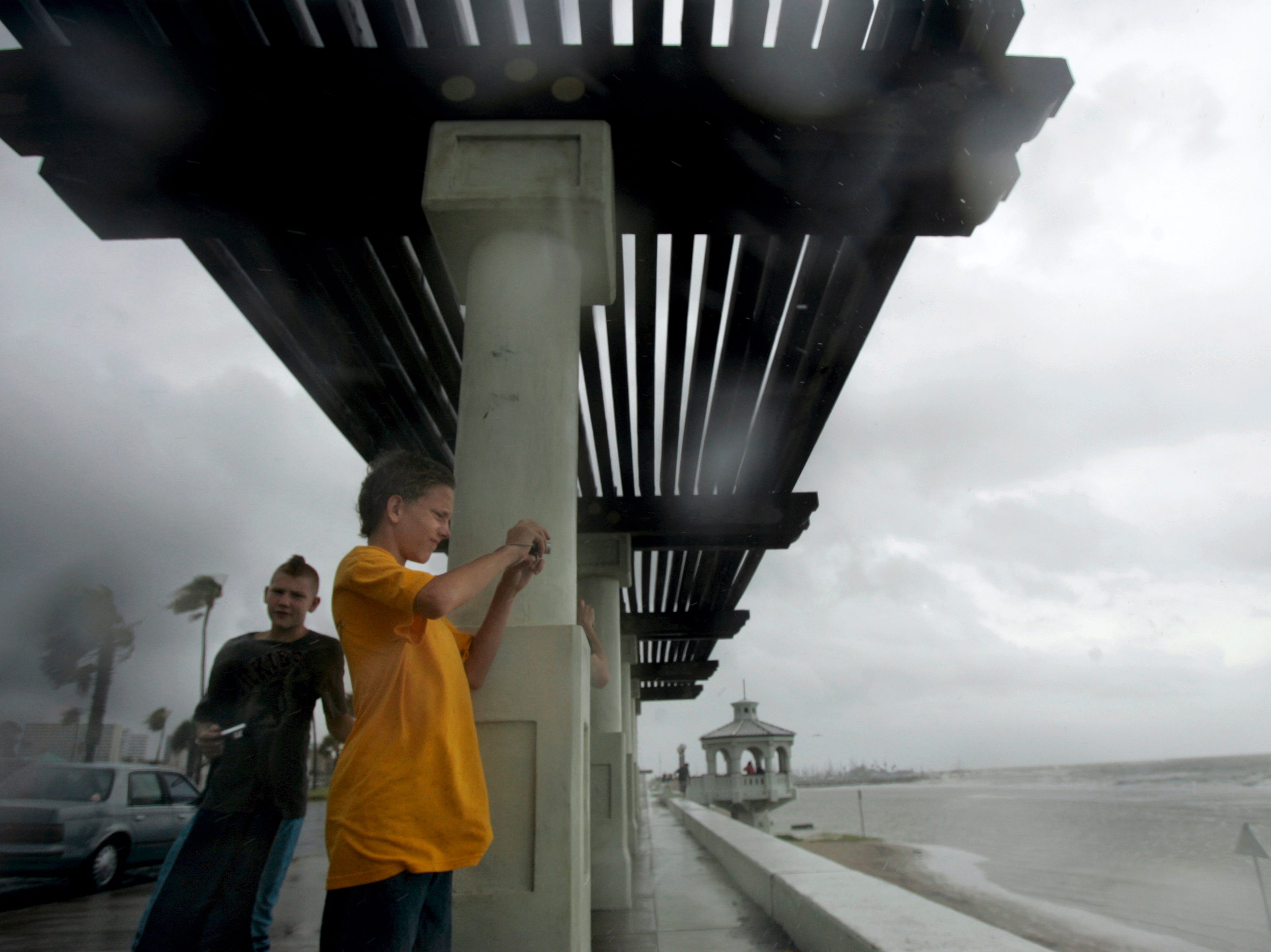 Rain starts to fall as Matthew Drye, 13 (left) and Zachary Wright,14, take pictures of the flooded McGee Beach area in downtown Corpus Christi on Wednesday, June 30, 2010. Bay waters rose as storm bands from Hurricane Alex hit the Coastal Bend.