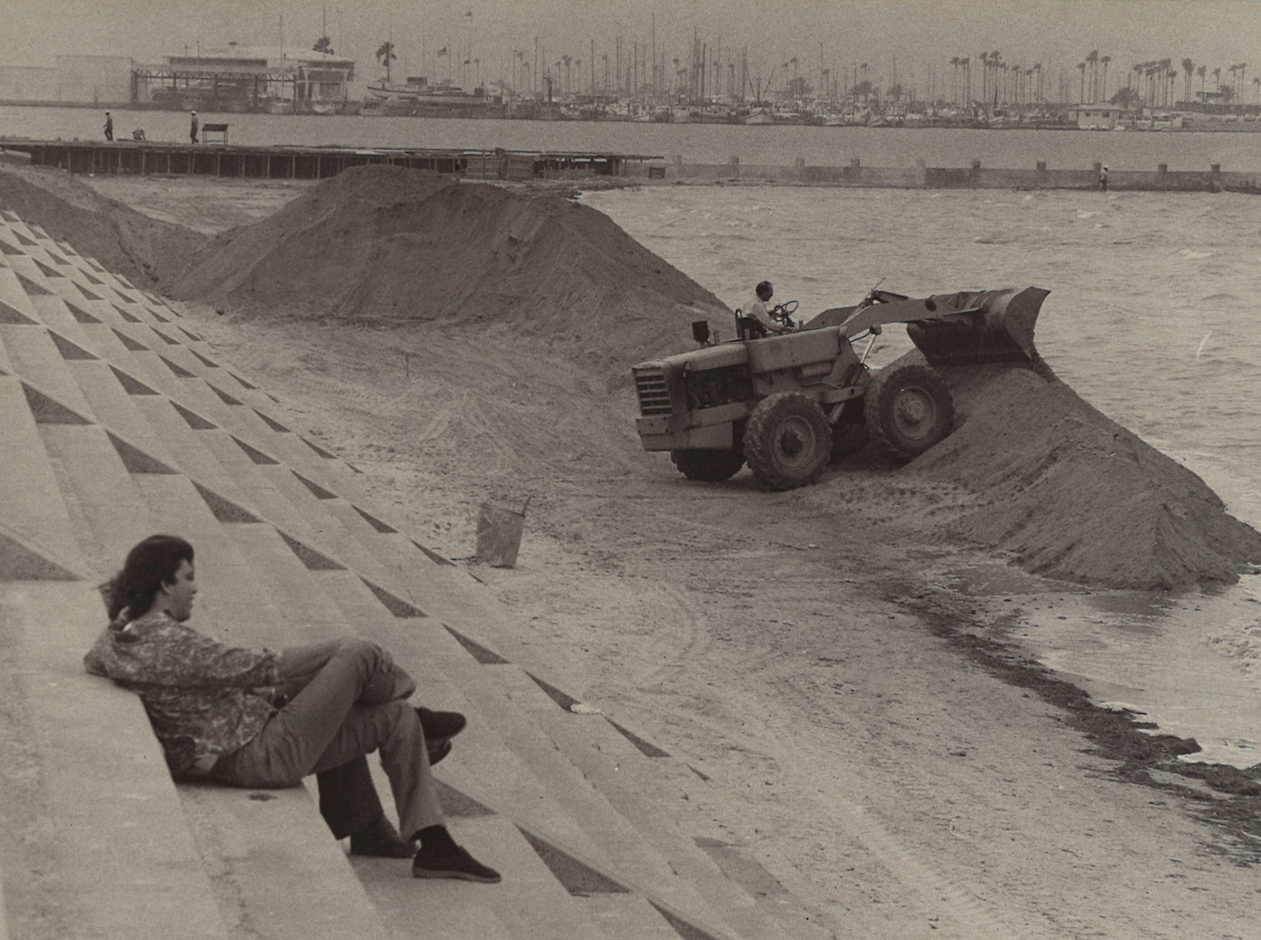 A man watches from the seawall as workers begin adding sand to McGee Beach in downtown Corpus Christi on May 7, 1975. About 4,500 cubic yards of sand taken from the banks of the Nueces River were added to the beach to widen it as part of a $350,000 improvement project that year. The elevated walkway in the background was being added to prevent the erosion of the sand.