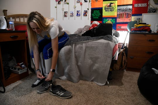 """Loren Kelly ties her shoes before softball practice, Thursday, March 21, 2019, in her apartment in Kingsville. Kelly visits her family in Rockport frequently. """"They're my number one supporters, I play for them and for my grandpa as well, Kelly said. If it wasn't for them I don't know if I'd even be playing anymore. I just like to spend time with family because I don't like to take things for granted like that."""""""