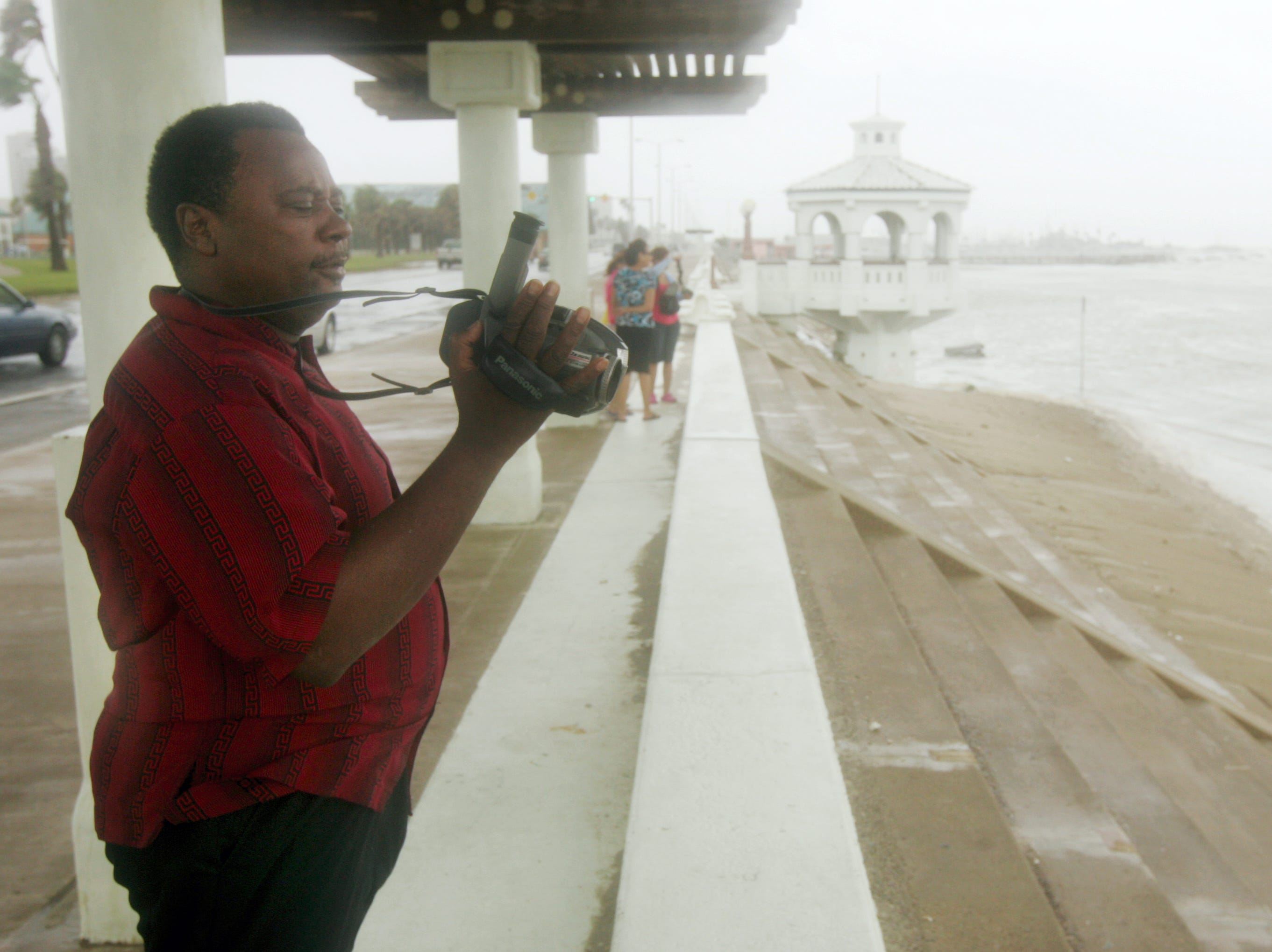 "The Rev. Mark Stewart, pastor at Star Baptist Church, records the scene at McGee Beach, were rising waters from Hurricane Dolly cover up the sand along the downtown bayfront in Corpus Christi on July 24, 2008. Stewart said he's lived here all his life and hasn't seen the beach like this. ""We were just down here the other day walking on the sand,"" he said. ""Seeing it today, its awesome."""