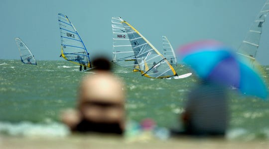Spectators on McGee Beach watch sailboarders racing at the Velocity Games on May 28, 2005 in downtown Corpus Christi.
