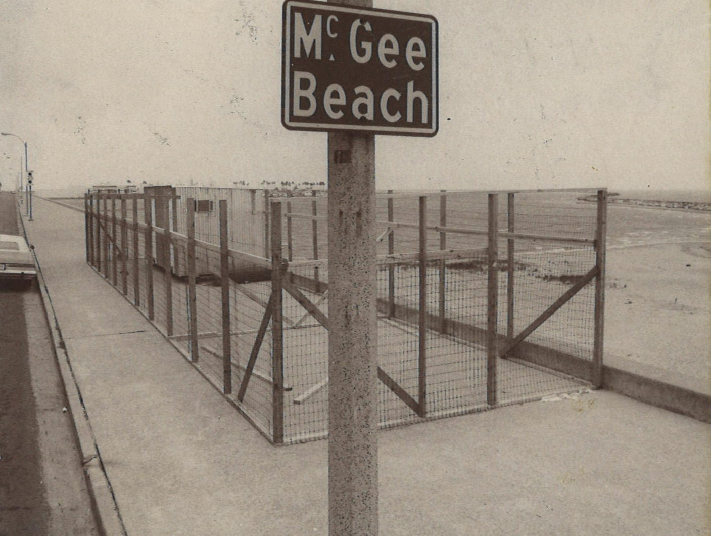 A barrier behind the sign for McGee Beach in downtown Corpus Christi shortly before improvement work began in March 1975.