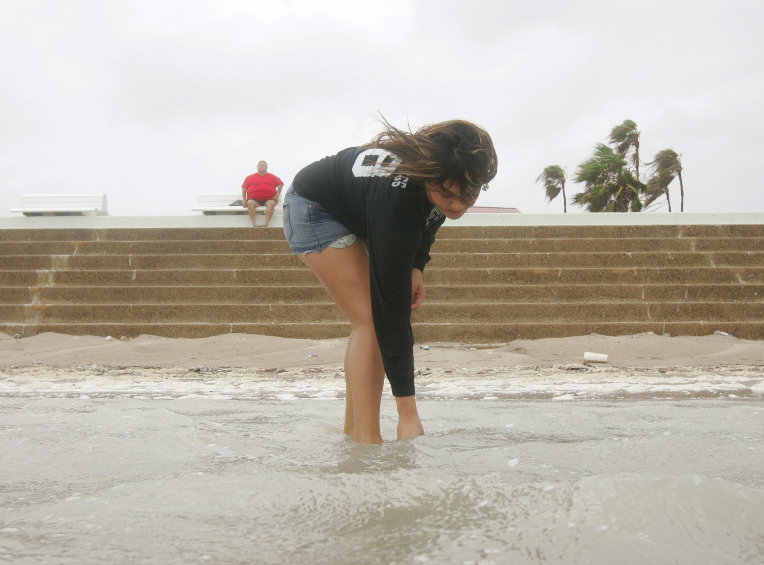 Tamie Rodela, 16 of Corpus Christi, picks up shells and rocks on McGee Beach Wednesday, July 23, 2008, flooded over from the high waters brought in by Hurricane Dolly in downtown Corpus Christi.