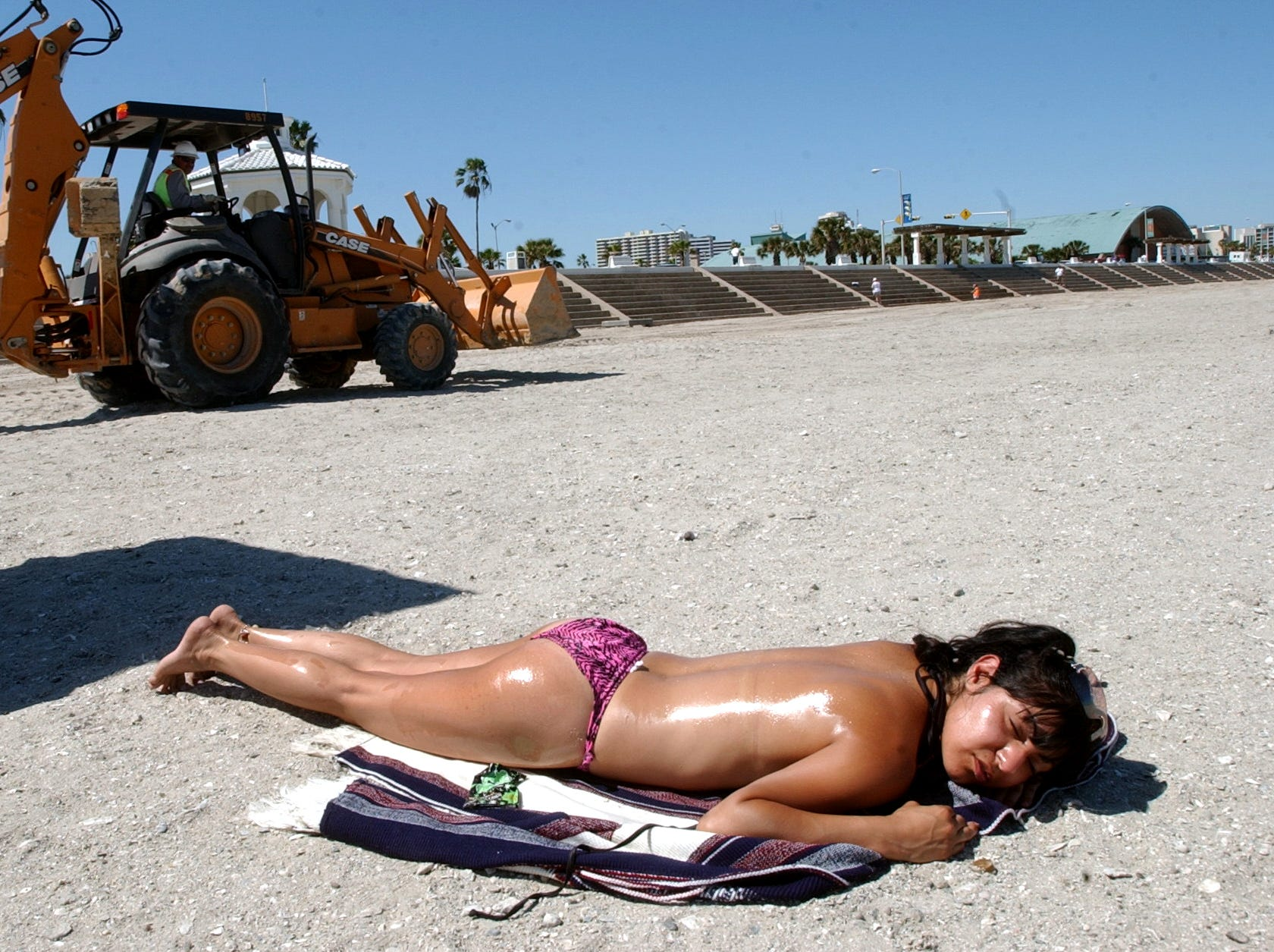 Monica Chavez from Los Angeles, Calif.,  enjoys McGee Beach in downtown Corpus Christi on Wednesday, March 31, 2004 as tractors rumbled by working on the seawall and restoring the beach with new sand.