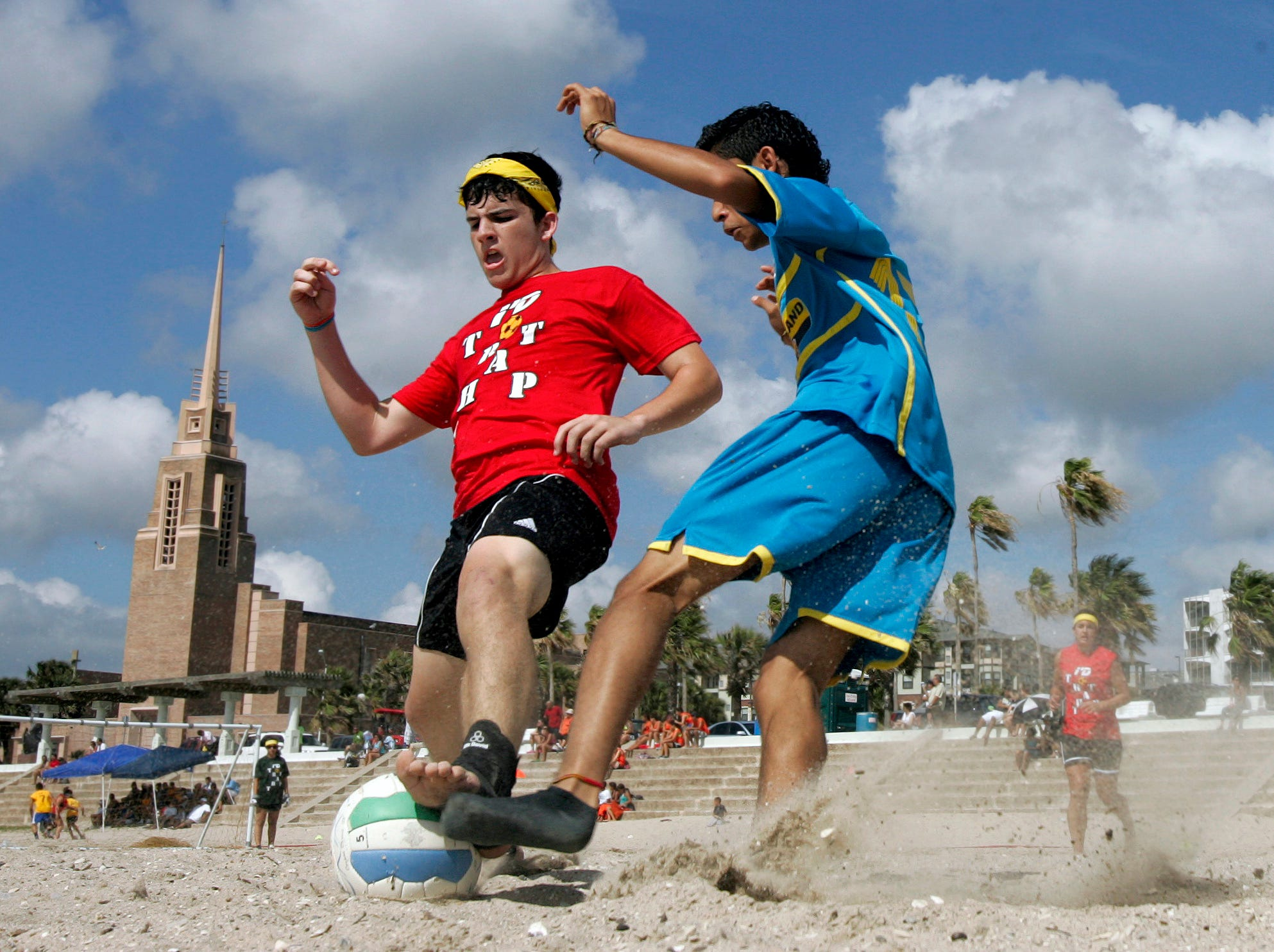 Kyle Thomson, 17 (left), fights for control of the ball with Joe Villanueva, 16, Saturday, June 19, 2010 during the Express Beach Soccer Fest on McGee Beach in downtown Corpus Christi. Participants aren't allowed to wear hard shoes, but many participants wear socks, wraps of aqua socks for traction and support.