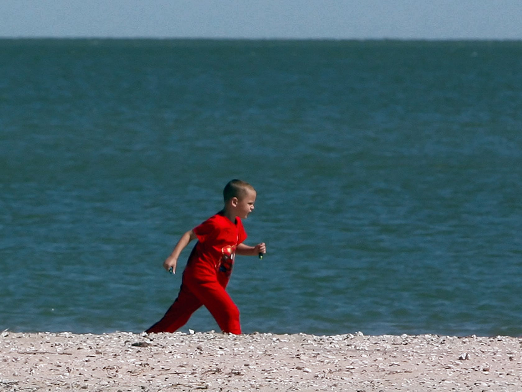 Cody Davidson, 5, visiting from Magnolia, enjoys the cool and sunny weather as he runs down McGee Beach to catch up with his family as they walk along the shoreline Tuesday, October 23, 2007.