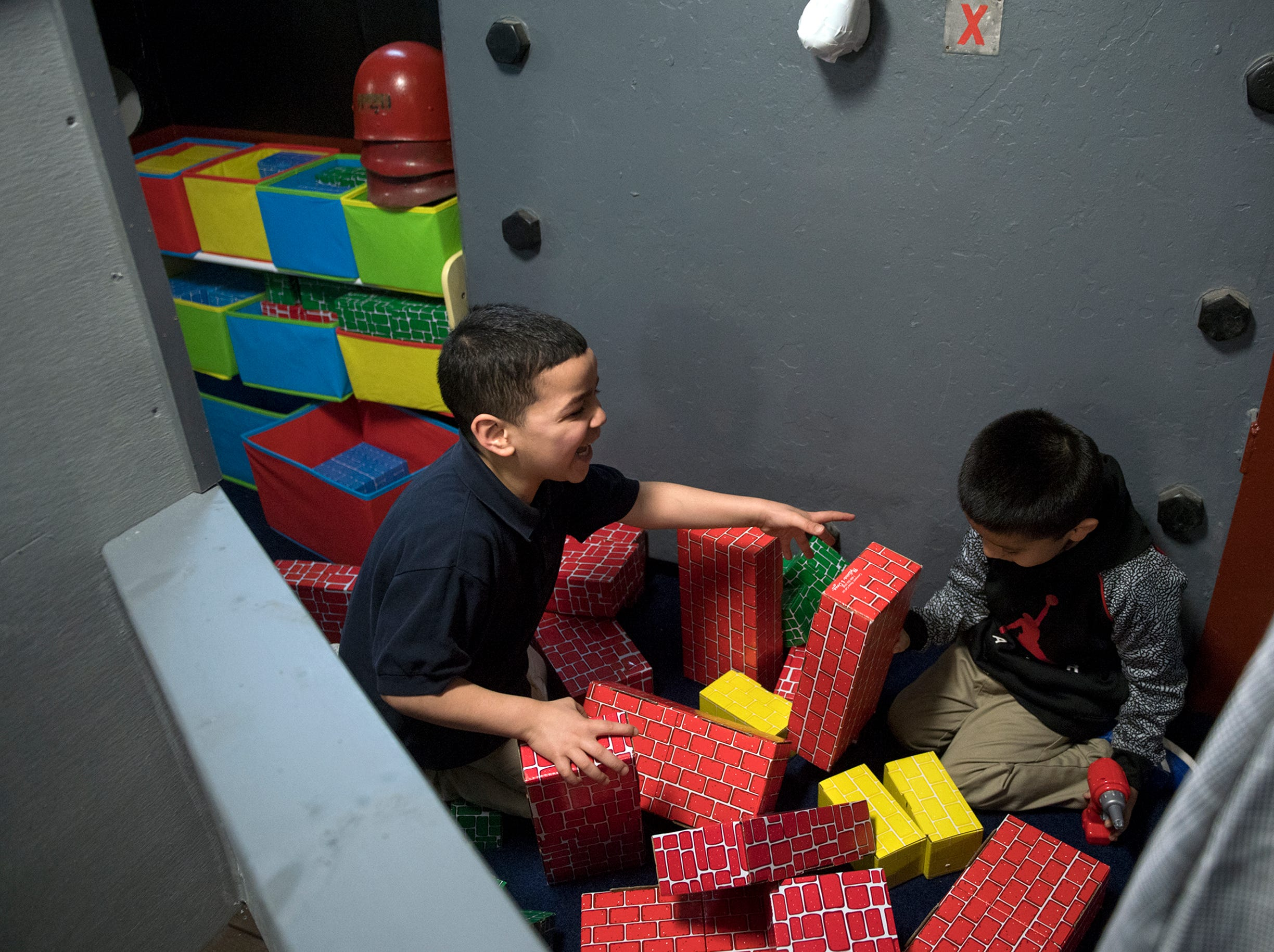 Pre-schoolers Joandel Feliciano, left, and Edward Tellez laugh as their brick wall collapses at Jason's Kids Kompartment Thursday, March 21, 2019 aboard the USS New Jersey battleship in Camden, N.J.