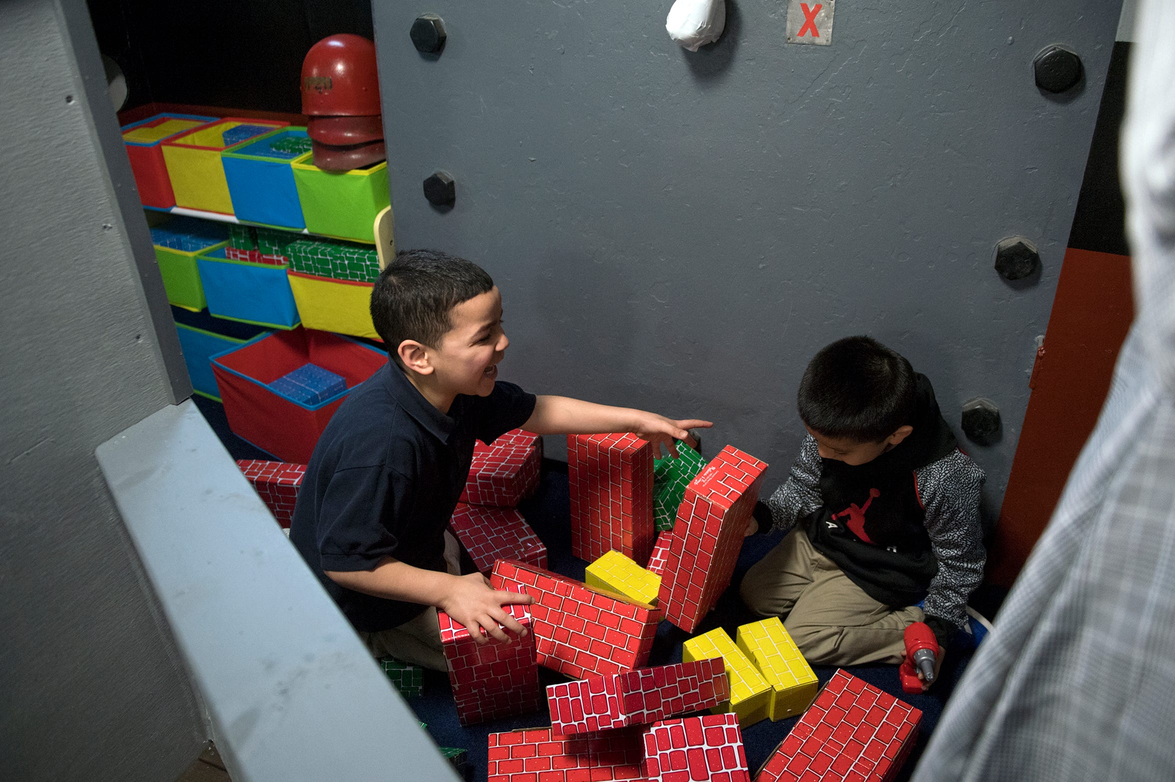 Pre-schoolers Joandel Feliciano and Edward Tellez laugh as their brick wall collapses at Jason's Kids Kompartment aboard the USS New Jersey battleship in Camden.