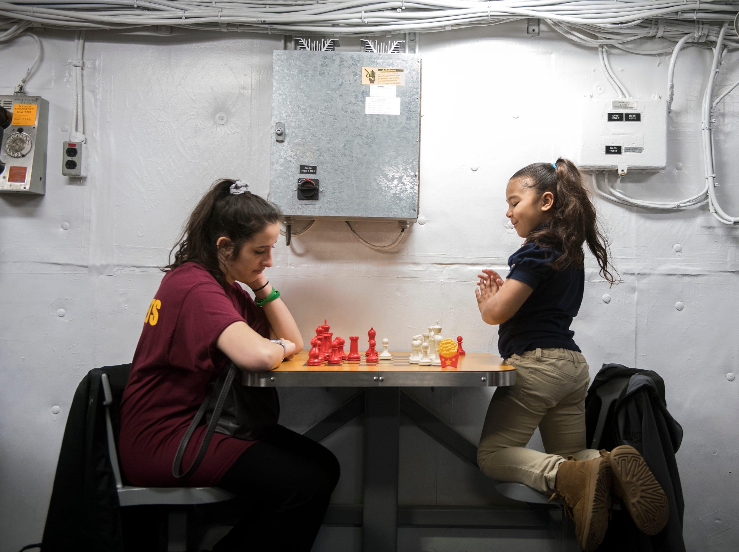 Student teacher Samantha Pagnani, left, and Oj'lynn Rivera, 5, play chess inside Jason's Kids Kompartment Thursday, March 21, 2019 aboard the USS New Jersey battleship in Camden, N.J.